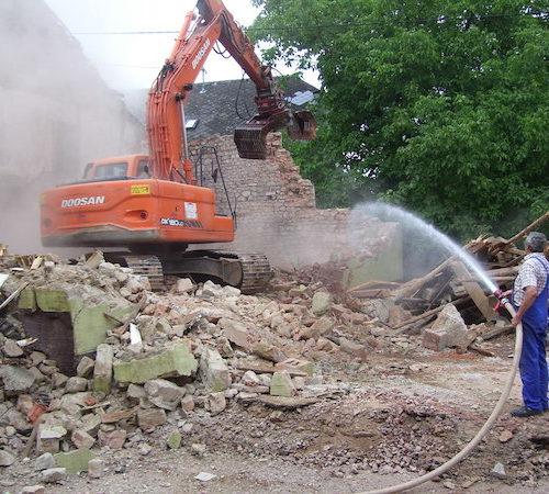 Ein Mann spritzt die Abbrucharbeiten eines Baggers an einer Mauer mit Wasser ab - Bauleistung