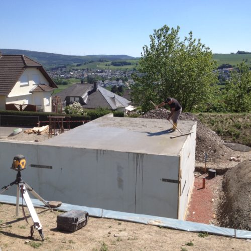 Mann begradigt das Dach bei Kellerbauarbeiten - Bauleistung