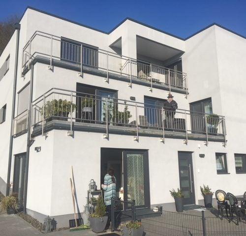 fertiggestellter Hausbau mit Balkonen und Terrasse - Bauleistung