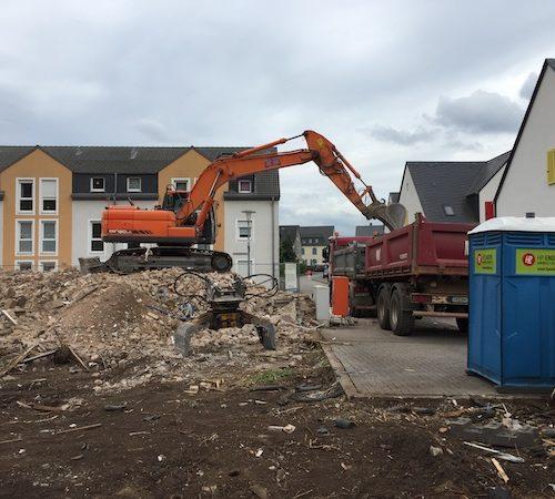Abbrucharbeiten mit Bagger und Laster inmitten von Häusern - Bauleistung