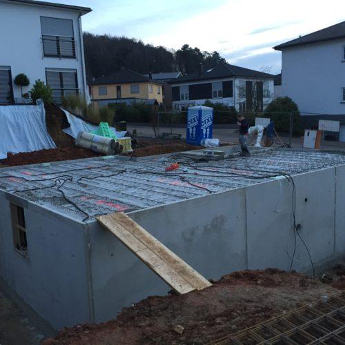Kellerbauarbeiten inmitten von Häusern auf einer Baustelle - Bauleistung