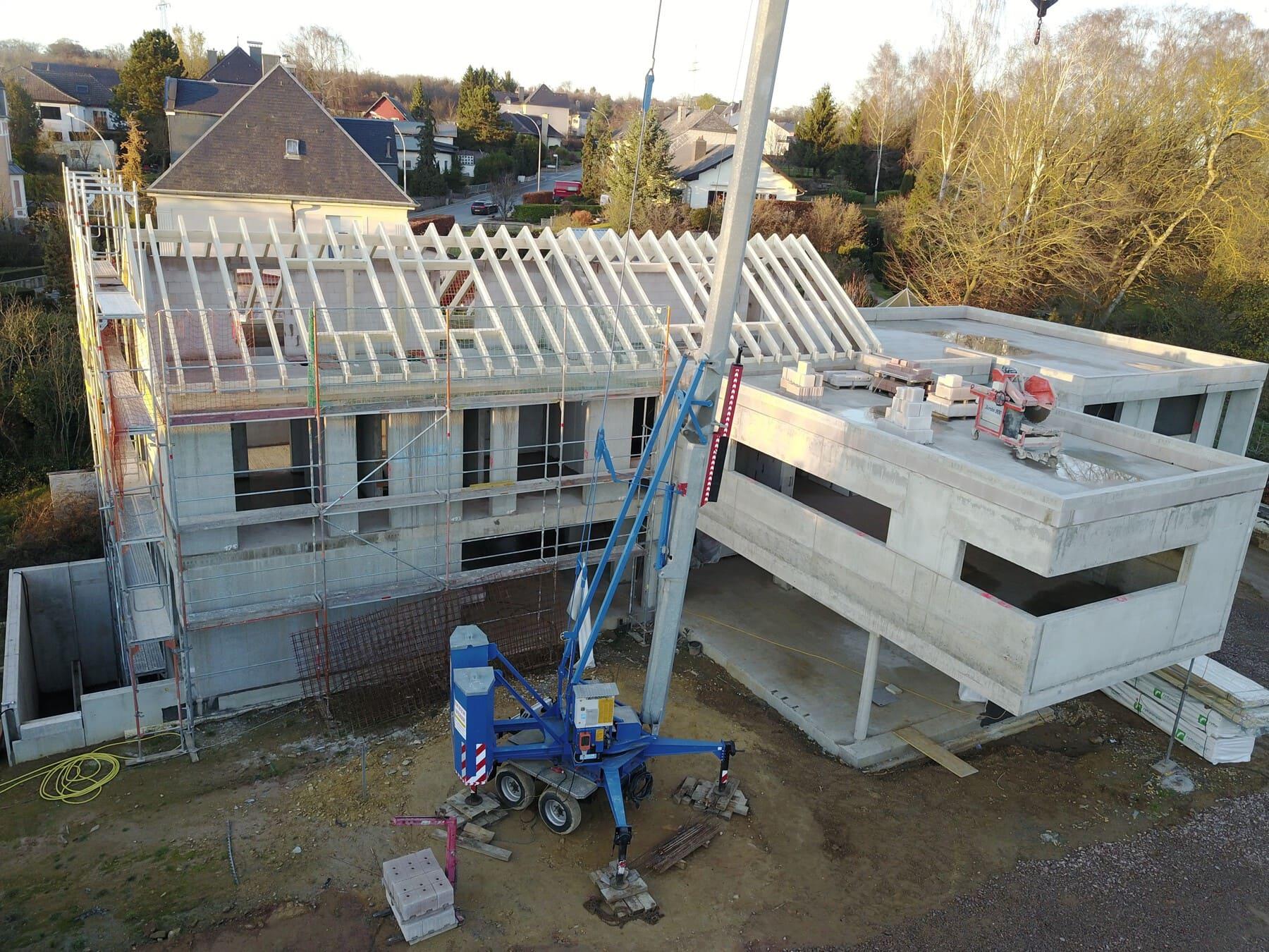 Rohbau eines Hauses und Baustelle mit Kran und Gerüsten - Bauleistung